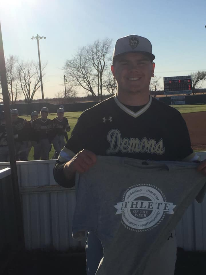 Winner of Impact Athlete of the Week, Dalton Spring, holding up his shirt after a baseball game.