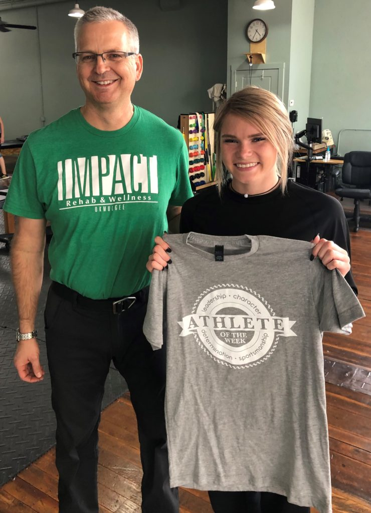 Winner of Impact Athlete of the Week, Bailee Worlow, holds up her shirt with physical therapist, Michael Siegenthaler.