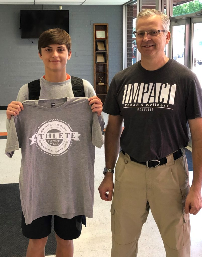 Winner of Impact Athlete of the Week, Ty Long, holds up shirt with physical therapist, Michael Siegenthaler.