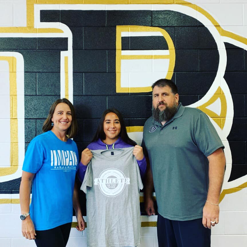 Athlete of the Week winner, Kaci Phelps, holding up her shirt. Also pictured are Kris Siegenthaler with Impact and Chad Stanton, Athletic Director at Beggs.