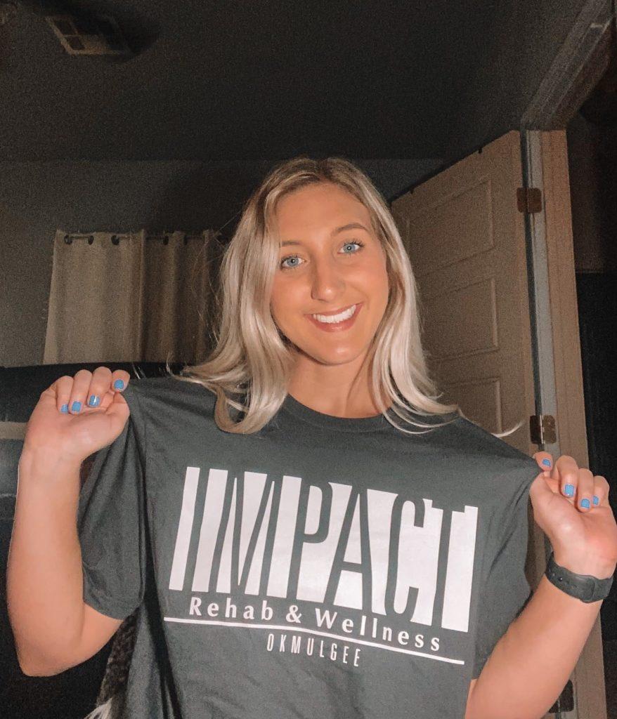 Gabby Tucker, PTA, new employee of Impact Rehab & Wellness, wearing her Impact shirt.